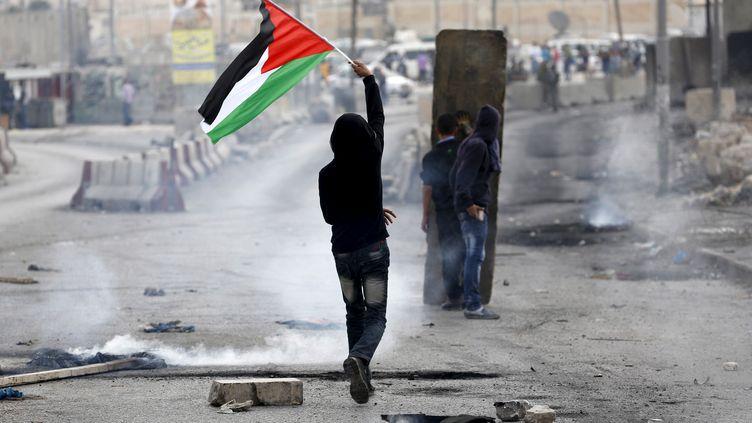 Un jeune Palestinien brandit son drapeau lors d'affrontements avec l'armée israélienne, le 6 octobre 2015, au check-point de Qalandia, près de Ramallah (Cisjordanie). (MOHAMAD TOROKMAN / REUTERS)