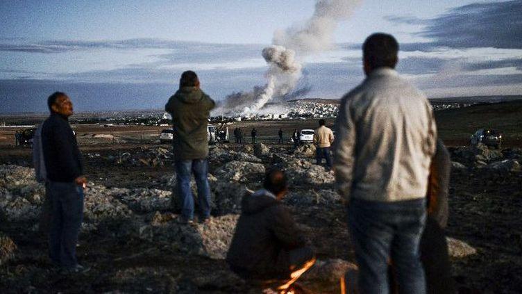 Des réfugiés kurdes regardent la ville de Kobané depuis la frontière turque. (AFP)