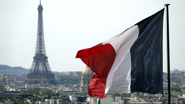 Un drapeau français avec en arrière-plan la Tour Eiffel. (ALEXANDRE MARCHI / MAXPPP)