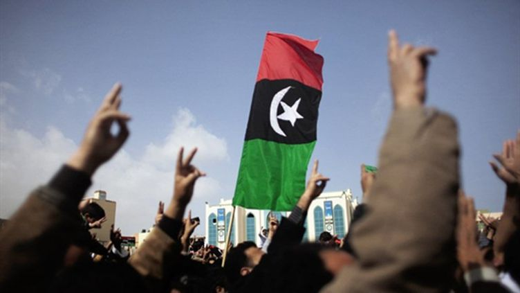 L'anciien drapeau lybien brandi comme symbole contre le régime de Mouammar Kadhafi (25/02/2011) (AFP/MARCO LONGARI)