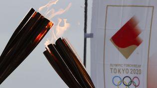 Lors du relais de la flamme olympique, le 14 juillet 2021 à Tokyo (Japon). (SHOTA OUCHI / PHOTO KISHIMOTO / AFP)