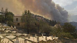 Un panache de fumée dégagé par un feu de forêt sur une colline près de Tizi Ouzou (Algérie), le 10 août 2021. (RYAD KRAMDI / AFP)