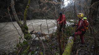 Des secouristes sur les rives du Bréda, à Détrier (Savoie), le 4 janvier 2018, à la recherche d'un pompier emporté par les flots. (PHILIPPE DESMAZES / AFP)