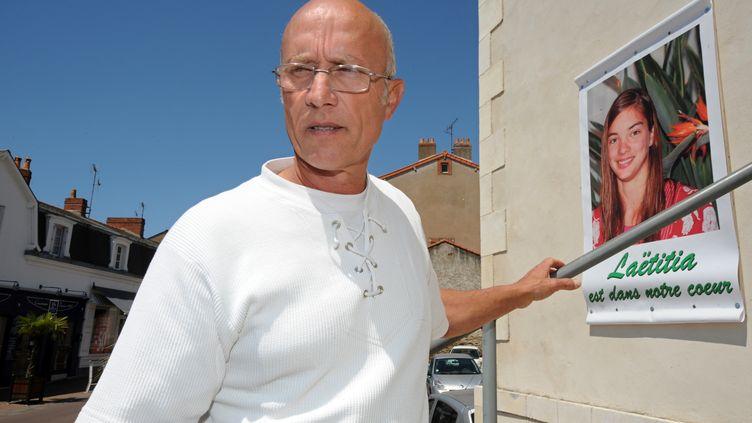 Gilles Patron, le père d'accueil de Laëtitia Perrais, le 22 juin 2011, derrière une photo de l'adolescente tuée près de Pornic (Loire-Atlantique) en janvier de la même année. (FRANK PERRY / AFP)