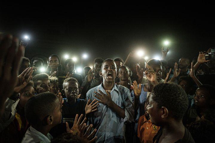 """Un homme récite un poème au milieu d'un groupe de manifestants à Khartoum, au Soudan. Une photo deYasuyoshi Chibadans le cadre de l'exposition """"L'Afrique de Chiba"""". (YASUYOSHI CHIBA / AFP)"""