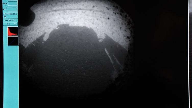 L'ombre du robot Curiosity projetée sur le sol de Mars et retransmise par un écran de la Nasa, le 6 août 2012, à Pasadena en Californie (Etats-Unis). (NASA / AFP)