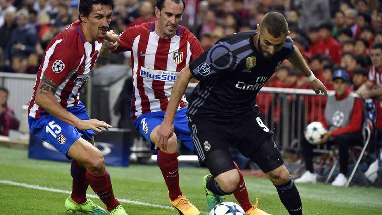 Karim Benzema dribble Godin et Savic lors de la demi-finale retour contre l'Atlético (GERARD JULIEN / AFP)
