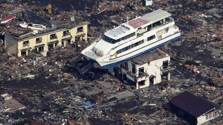 Une photo aérienne montre un bateau échoué sur le toit d'un immeuble au milieu d'une mer de débris dans la ville deOtsuchi, dans la prefecture d'Iwate, trois jours après les catastrophes naturelles qui ont endommagé la centrale nucléaire de Fukushima-Daiichi. «Le vendredi 11 mars 2011, à 5h46 TU (14h46 heure locale), un séisme de magnitude 9,0 se produit à 80 km à l'est de l'île d'Honshu au Japon», peut-on lire sur le site de l'Institut (français) de radioprotection et de sûreté nucléaire. «Ce séisme a généré un tsunami de grande ampleur» qui a conduit «à l'arrêt des quatre centrales nucléaires les plus proches de l'épicentre». «Le tsunami a entraîné la perte des systèmes de refroidissement des centrales de FukushimaDaiichi et Fukushima Daini,occasionnant un accident nucléaire avec relâchement de radioactivité.»  Ces catastrophes sont à l'origine de la mort de plus de 19.000 personnes, dont la majorité est morte noyée. En outre, indique Reuters, «plus de 160.000 personnes ont été évacuées des villes situées autour de la centrale et près de 10% d'entre elles vivent dans des logements temporaires disséminés dans la circonscription territoriale de Fukushima». De même, l'accident nucléaire de Fukushima pourrait provoquer «10.000 cancers de plus dans la population japonaise en raison des radiations, selon un rapport de deux ONG publié (mercredi 9 mars 2016) aux Etats-Unis», rapporte l'AFP.         .   (YOMIURI SHIMBUN / AFP)