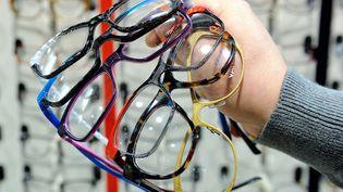 Un opticien présente des paires de lunettes, àWattignies (Nord), le 16 décembre 2013. (PHILIPPE HUGUEN / AFP)
