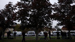 Policiers et journalistes le 17 octobre 2020 devant le collège de Conflans-Sainte-Honorine, où enseignait Samuel Paty. (YOAN VALAT / EPA / MAXPPP)