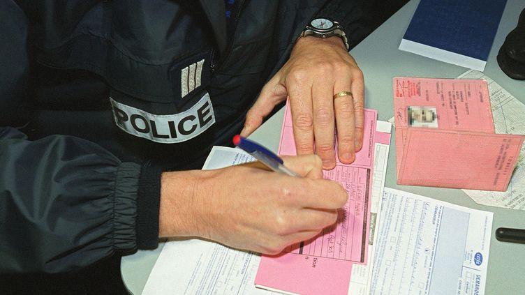 Un policier verbalise un automobiliste. Le nouveau fichier a été autorisé par la Cnil. (FREDERICK FLORIN / AFP)