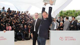 Benoît Poelvoorde (D), toujours aussi ingérable, a démonté le pupitre durant le photocall en compagnie de son réalisateur Benoît Delépine. (VALERY HACHE / AFP)
