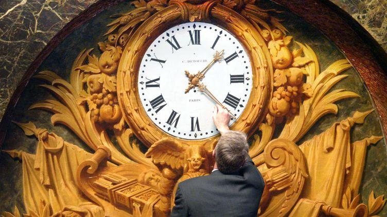 Un homme change l'heure sur l'une des horloges du château de Versailles (Yvelines), le 17 mars 2003. (THOMAS COEX / AFP)