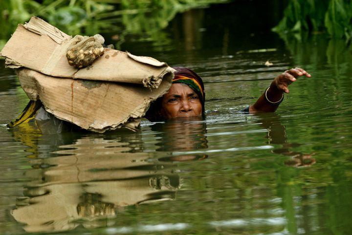 Une femme tente d'aller mettre au sec quelques affaires récupérées dans sa maison inondée. Sariakandi, district de Bogra, Bangladesh, 30 juillet 2007.  (© Abir Abdullah)
