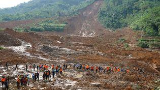 Des sauveteurs s'activent sur le lieu du drame, le 13 décembre 2014 à Jemblung (Indonésie). (HIMAWAN / AFP)