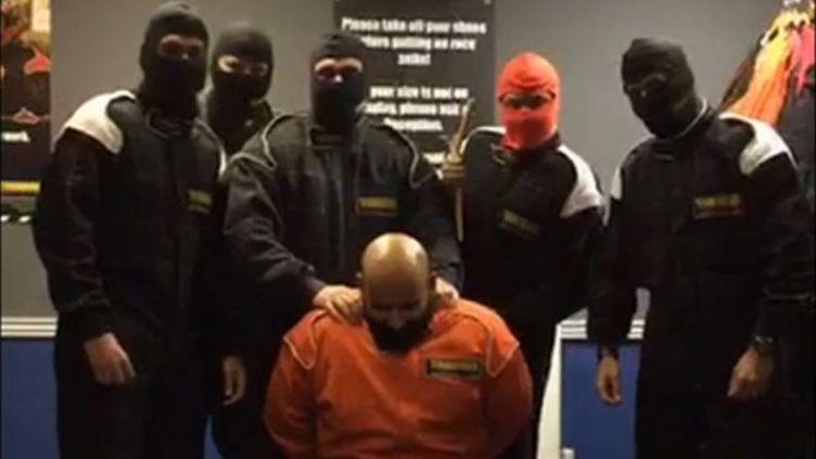 """Capture d'écran d'une vidéo relayée par """"The Sun"""", le 6 juillet 2015, montrant des employés britanniques de HSBC imiter une exécution de l'Etat islamique. (THE SUN / FRANCETV INFO)"""