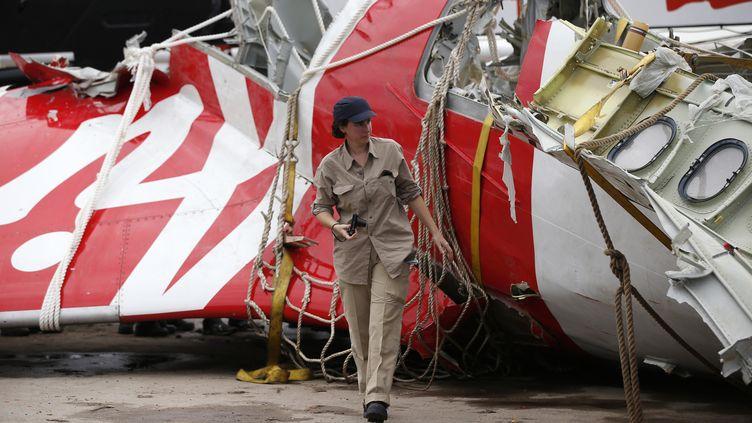 Un enquêteur d'Airbus marche,le 12 janvier 2015, à côté d'un morceau de l'avion d'AirAsiaéchoué en mer. (DARREN WHITESIDE / REUTERS)