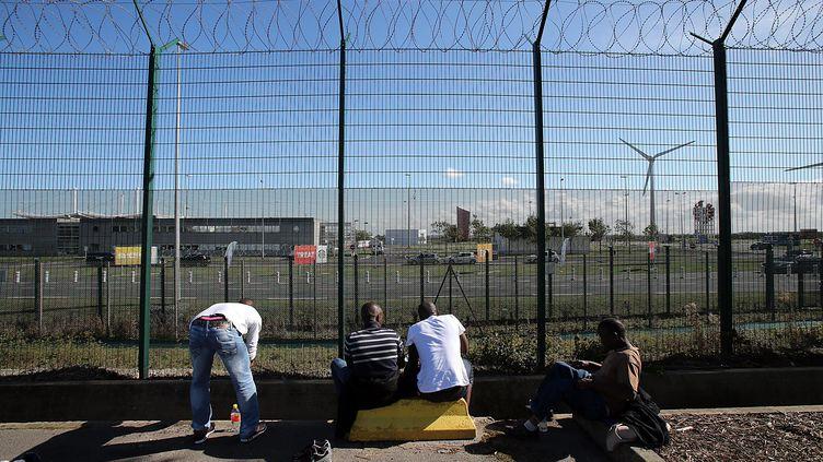 Des migrants attendent devant les grilles du tunnel sous la Manche, le 26 septembre 2015, à Calais (Pas-de-Calais). (MAXPPP)