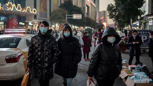 Des passants à Wuhan (Chine), le 13 janvier 2021. (NICOLAS ASFOURI / AFP)
