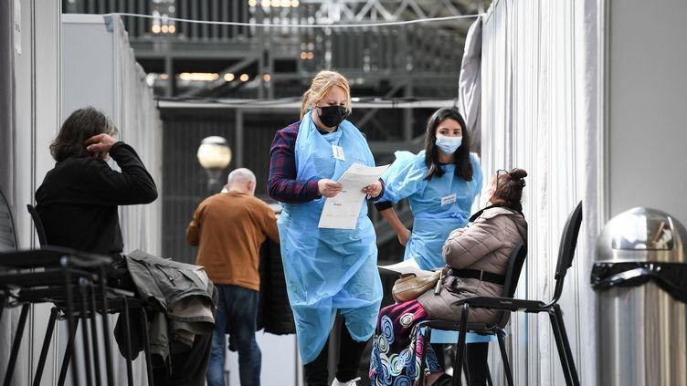Des soignants discutent avec des patients avec leur vaccination contre le Covid-19, dans un centredu 19e arrondissement de Paris, en avril 2021. (ALAIN JOCARD / AFP)