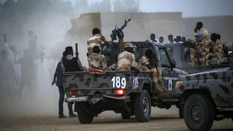Des membres de la Force de soutien rapide du Soudan sont à l'arrière d'une camionnette équipée d'une tourelle de mitrailleuse lors d'un rassemblement dans le village de Qarri, à environ 90 kilomètres au nord de Khartoum, le 15 juin 2019. (- / AFP)