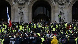 """Des """"gilets jaunes"""" rassemblés devant l'opéra Garnier, le 15 décembre 2018, à Paris. (GEOFFROY VAN DER HASSELT / AFP)"""