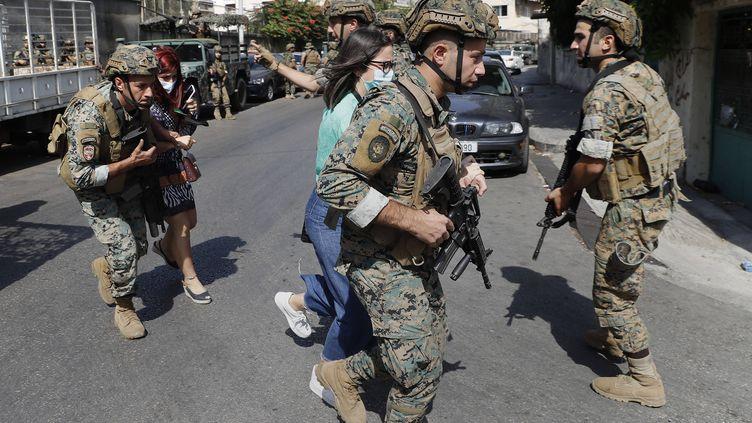 Des soldats libanais protègent des enseignants fuyant leur école après des tirs lors d'une manifestationcontre le juge chargé de l'enquête sur l'explosion au port de Beyrouth, le 14 octobre 2021 à Beyrouth (Liban). (HUSSEIN MALLA / AP / SIPA)