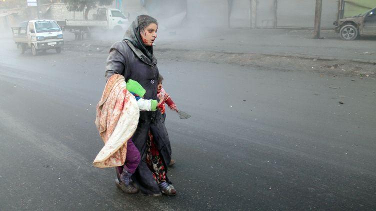 Une femme blessée et ses enfants dans une rue d'Alep (Syrie), le 15 décembre 2013. (MOHAMMED AL-KHATIEB / AFP)