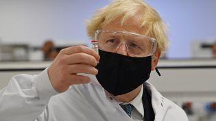 Le Premier ministre britannique Boris Johnson pose avec un flacon du vaccin d'AstraZenecacontre le Covid-19, au Pays de Galles le 30 novembre 2020. (PAUL ELLIS / POOL / AFP)