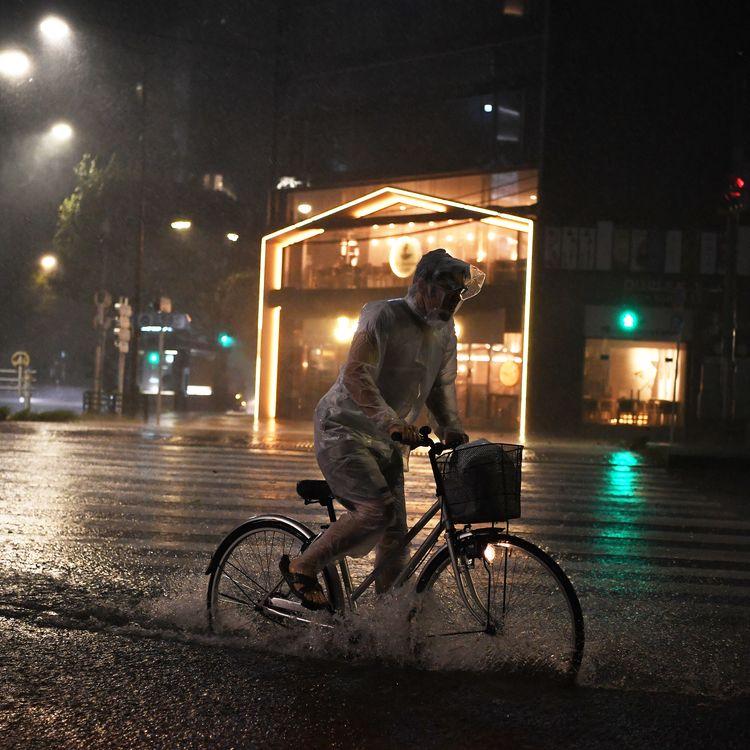 Un cycliste tente de faire fasse à la pluie et au vent dans les rues de Tokyo (Japon), le 9 septembre 2019. (CHARLY TRIBALLEAU / AFP)