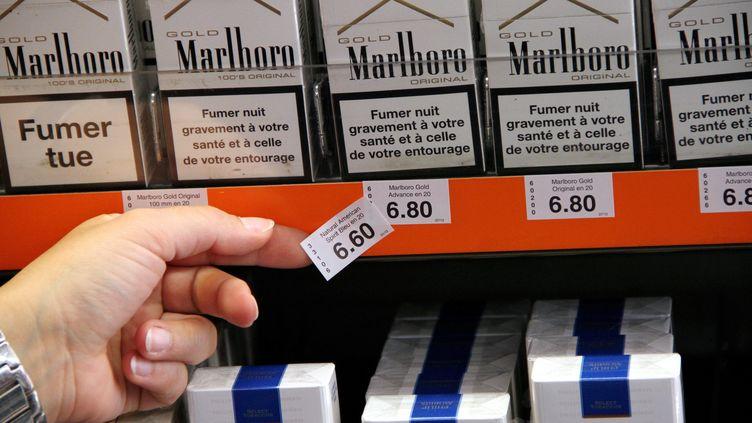 Une buraliste change les étiquettes de prix des paquets de cigarettes, le 15 juillet 2013 à Thionville (Moselle). ( MAXPPP)