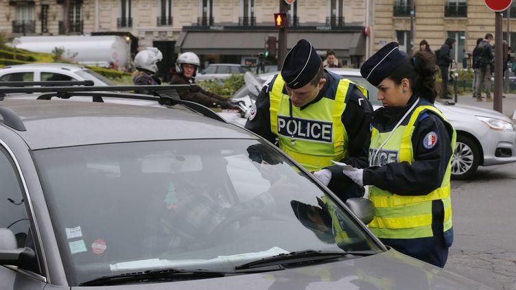 Des policiers contrôlent un automobiliste à Paris, le 14 mars 2014. (FRANCOIS GUILLOT / AFP)
