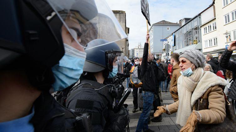 Une manifestante confrontela police lors d'un rassemblement à Cassel (Allemagne), le 20 mars 2021. (SWEN PFORTNER / DPA / AFP)