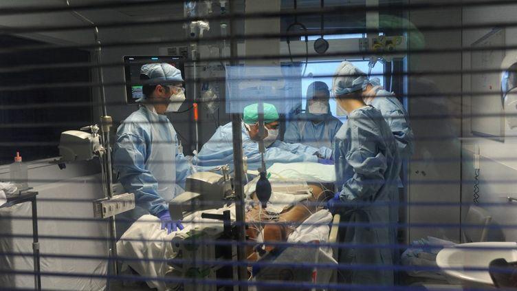 Des soignants prennent en charge un malade, dans une unité dédiée au Covid-19, dans un hôpital français, en avril 2020. (PASCAL BACHELET / BSIP / AFP)