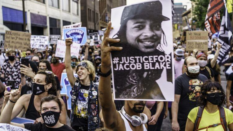 Des manifestants à Minneapolis (Minnesota), brandissent le portrait de Jacob Blake, le 24 août 2020. (KEREM YUCEL / AFP)