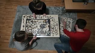 Une famille confinée fait un puzzle à Dortmund (Allemagne) le 27 mars 2020 (INA FASSBENDER / AFP)