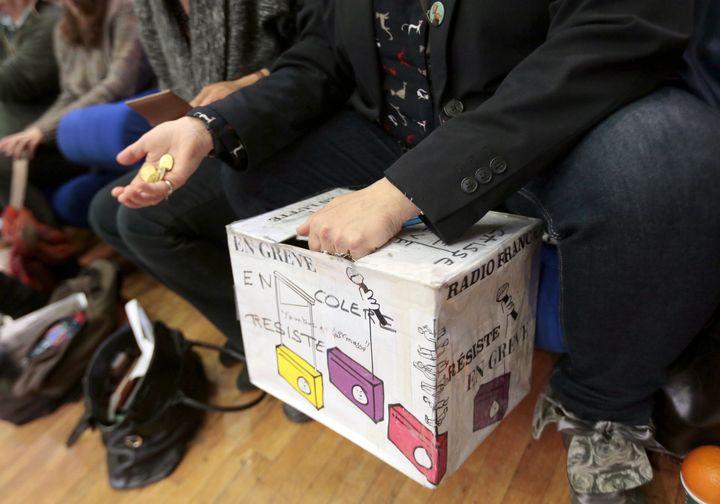 Un salarié gréviste de Radio France collecte de l'argent dans la caisse de grève, le 3 avril 2015 à la Maison de la radio à Paris, lors d'une assemblée générale. (JACQUES DEMARTHON / AFP)