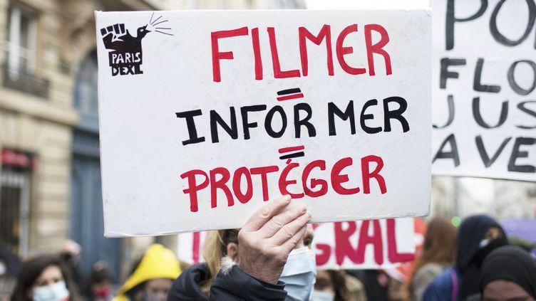 Une pancarte brandie lors d'une manifestation contre le projet de loi relative à la sécurité globale et pour la liberté de la presse, à Paris, le 16 mars 2021. (FIORA GARENZI / HANS LUCAS)