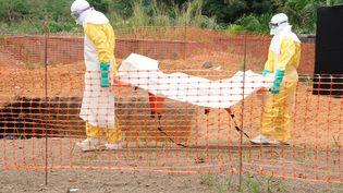 Du personnel médical de Médecins sans frontières transporte le corps d'une victime du virus Ebola, à Guéckédou (Guinée), le 1er avril 2014. (SEYLLOU / AFP)