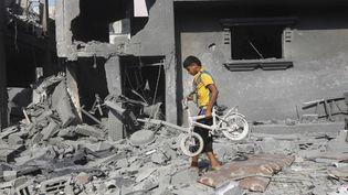 Un enfant palestinien fouille les décombres de sa maison à Rafah (Gaza), le 2 août 2014. (SAID KHATIB / AFP)
