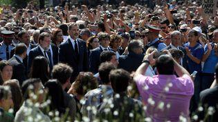 Le roi d'Espagne Felipe VI (à gauche), le Premier ministre espagnol Mariano Rajoy (au centre) et le président du gouvernement catalan, Carles Puigdemont (à droite), attendent côte à côte avant d'observer une minute de silence sur la Place de Catalogne (Espagne), le 18 août 2017, en hommage aux victimes des attentats perpétrés la veille en Catalogne. (LLUIS GENE / AFP)