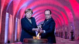 François Hollande et Angela Merkel allument une flamme de la mémoire, le 29 mai 2016, à Douaumont (Meuse). (KAY NIETFELD / DPA / AFP)