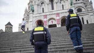 La police municipale patrouille dans les rues, le 19 mars 2020, pour demander aux gens de rentrer chez eux, à Montmartre, à Paris, lors du troisième jour du confinement décrété par le gouvernement. (HUGO PASSARELLO LUNA / HANS LUCAS / AFP)