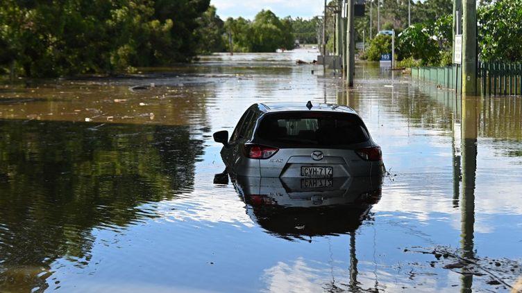 Une voiture piégée par les eaux dans le nord-est de Sydney (Australie), le 24 mars 2021. (STEVEN SAPHORE / ANADOLU AGENCY / AFP)