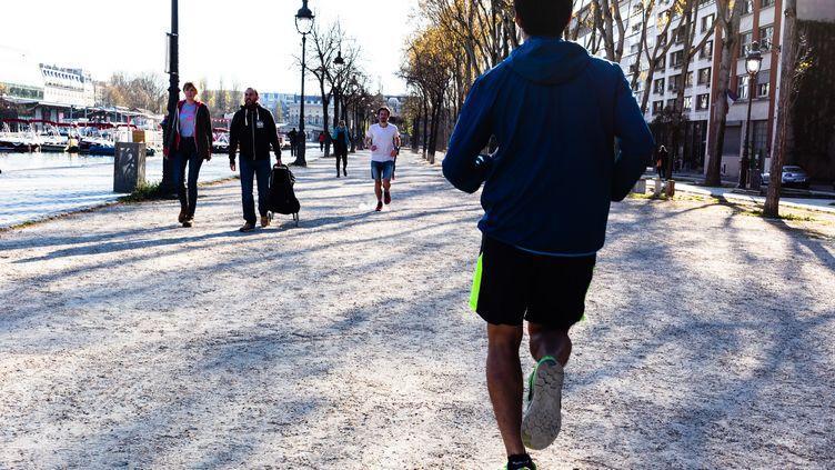 Coureurs le long du bassin de la Villette, à Paris (19e), le 4 avril 2020. (AMAURY CORNU / HANS LUCAS / AFP)