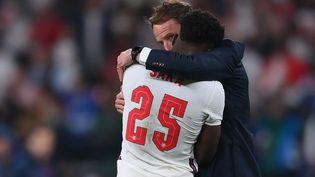 Le sélectionneur anglais Gareth Southgate avec Bukayo Saka, après la finale de l'Euro 2021 perdue contre l'Italie, dimanche 11 juillet. (LAURENCE GRIFFITHS / POOL / AFP)