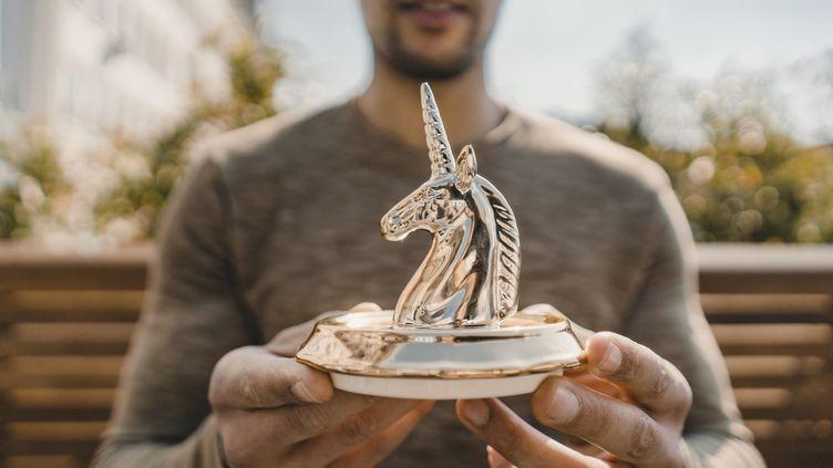 Jeune entrepreneur tenant une figurine en forme de licorne. (Illustration) (GETTY IMAGES / WESTEND61)