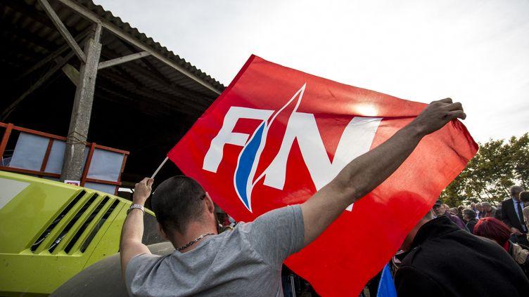 Un homme brandit un drapeau Front national lors d'un meeting de Marine Le Pen, le 30 mars 2017 àTrinité-Porhoët (Morbihan). (MARTIN BERTRAND / AFP)