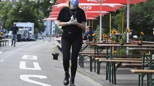 Une femme porte un masque sanitaire à Cologne (Allemagne), lors d'une fête, le 17 juillet 2020. (ROBERTO PFEIL / DPA / AFP)