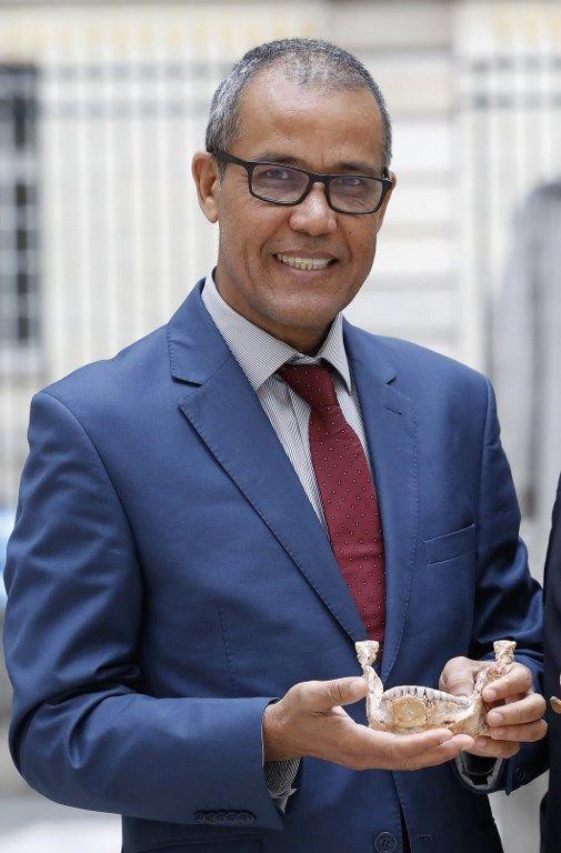 Abdelouahed Ben-Ncer de l'Institut National Institute d'Archaeologie du Maroc avec une mandibule d'Homo sapiens  (PATRICK KOVARIK / AFP)